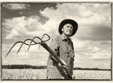 Old image with white frame of senior man working with hayfork in ripe barley field