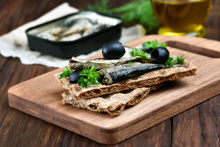 Sprats on crispbread on wooden cutting board