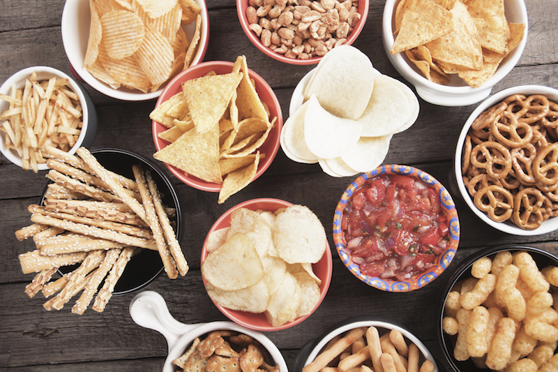 Salty crackers, tortilla chips and other savoury snacks with salsa dip