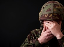 British soldier with both hands covering his face, against a black background.