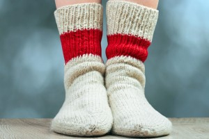 clouseup legs with pair wool knitted socks. Green grass behind